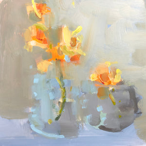 spring daffodils in a glass vase and a bluey gray pot.