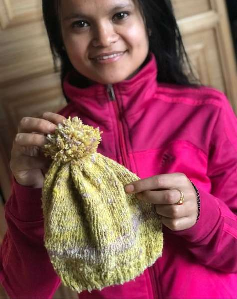 Rida holding the first zero waste beanie - Muezart