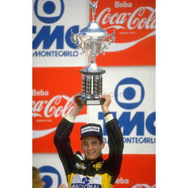 Lotus Renault driver Ayrton Senna celebrates with the trophy after his victory in the Brazilian Grand Prix at the Rio circuit | TotalPoster