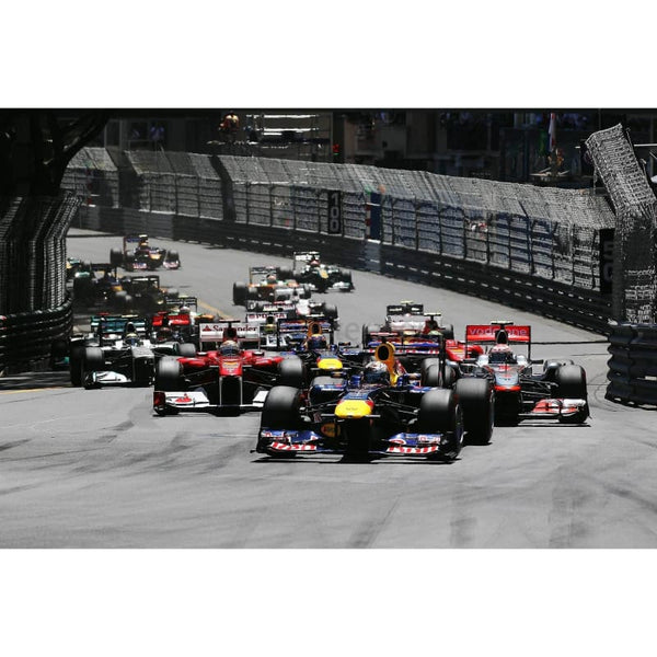 Sebastian Vettel / Red Bull Racing leads the field into S Devote at the start of the Monaco Formula One Grand Prix at the Monte Carlo Circuit | TotalPoster