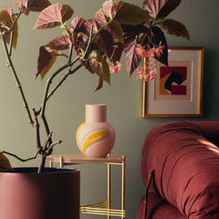 Pink, blue and yellow vase sitting on a side table in a living room