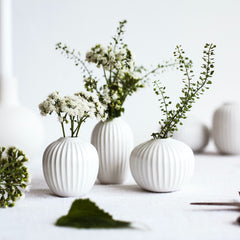Three white bud vases with spring white blossoms.