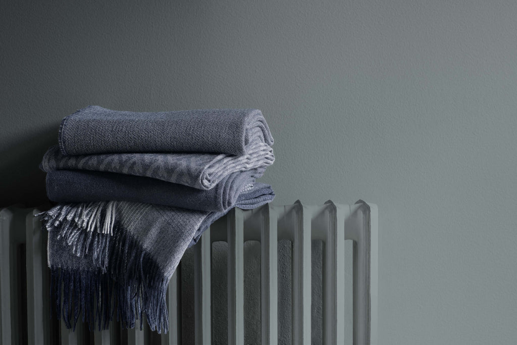 Stack of navy blue alpaca throws sitting on a radiator.