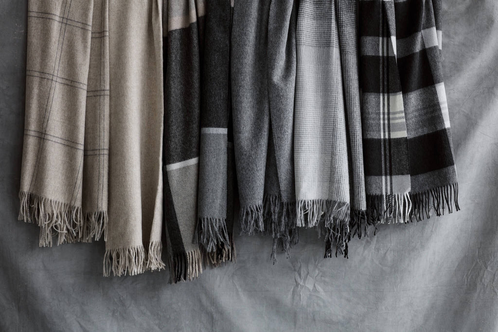 Six throws hanging against a gray backdrop. There are beige and gray and black throws that range from solid to plaid to check.