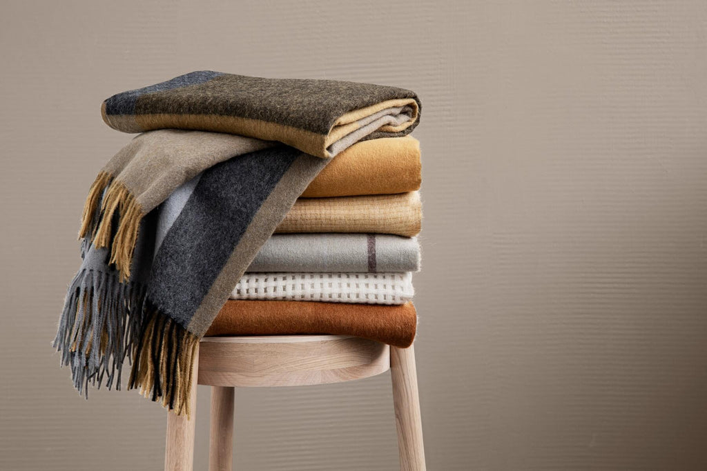 Pile of alpaca throw blankets on a wooden stool and in front of a beige wall. All the throws are orange or cream in tone and are solids and plaids.