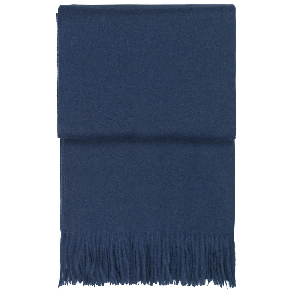 A dark blue alpaca throw blanket is folded on a white background.