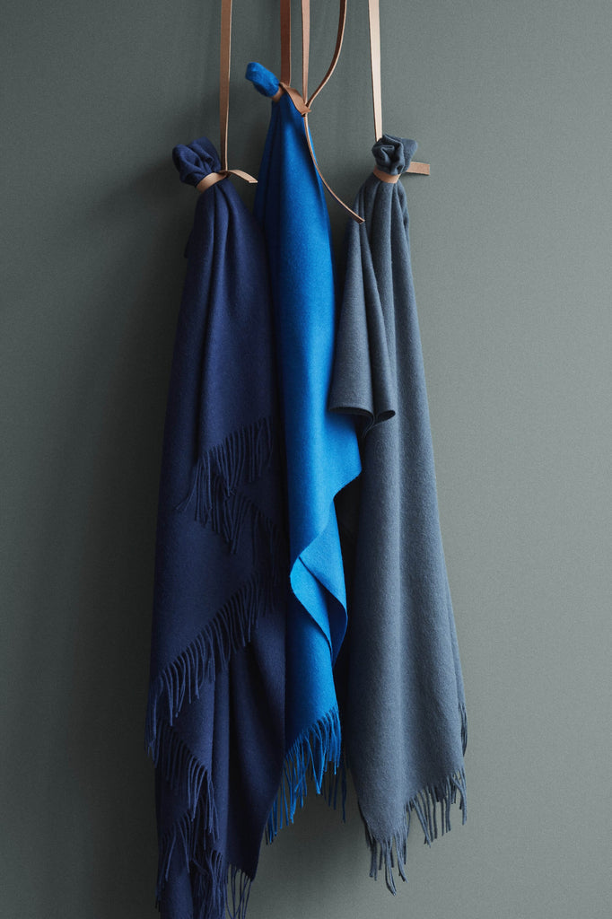 Three blue colored throw blankets are hanging from leather straps. The first is a dark, navy blue. The second a bright blue and the third a blue gray color.
