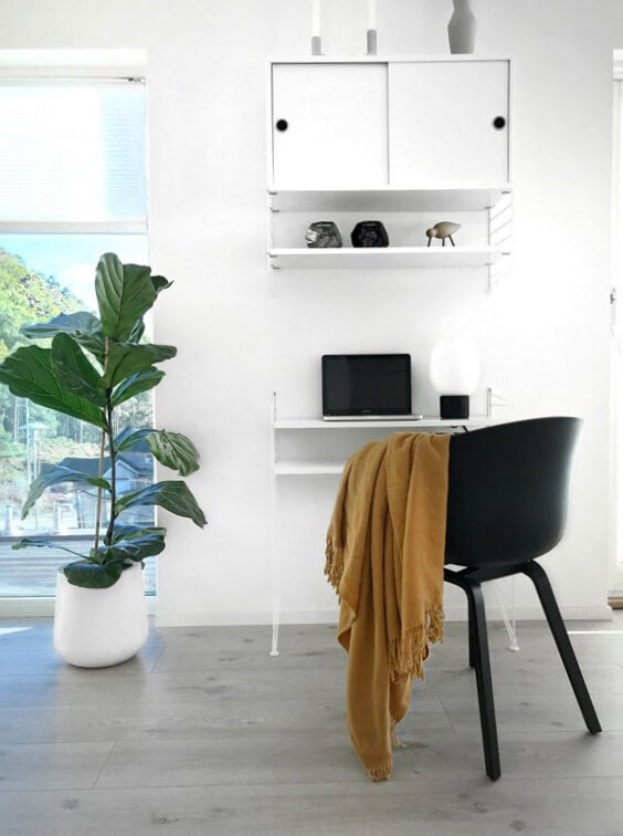A home office scene. There's white walls, a white desk with shelves and a leafy plant in a white pot. The only color comes from a black desk chair and a yellow ochre throw blanket draped over its arm.