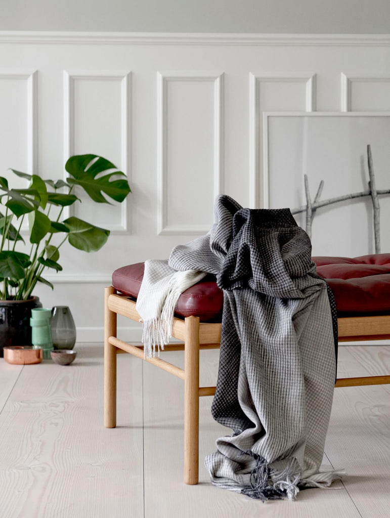 A gray ombre throw is dapped on a red leather and wood bench.
