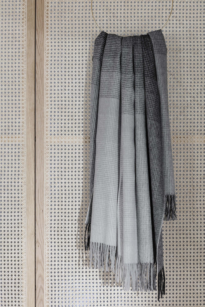 Gray ombre alpaca throw blanket hangs from a loop on a wood screen.