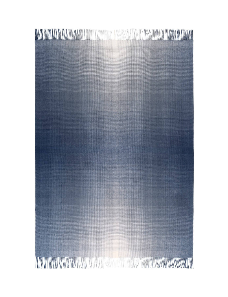 A dark blue ombre throw blanket laying flat on a white background.