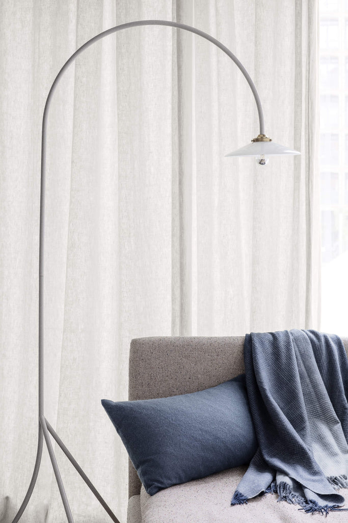 Room scence with a gray couch. A navy ombre throw is draped over the back of the sofa and there's a matching dark blue throw pillow. A floor lamp overhangs the couch.