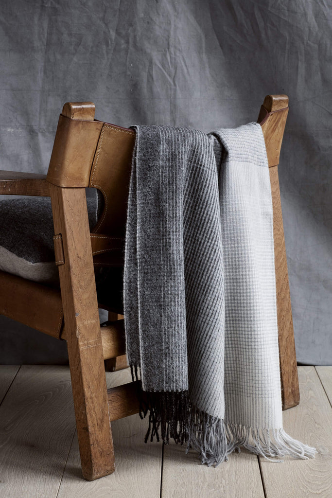 Gray alpaca throw blanket draped over the back of a wood and leather chair.
