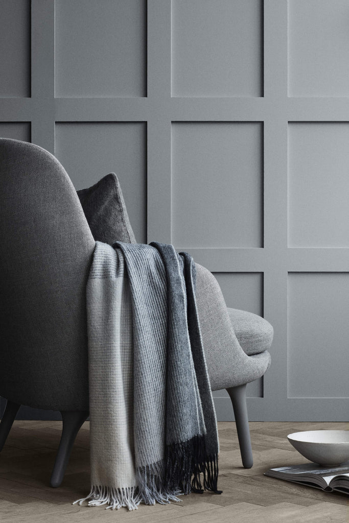 Gray throw blanket draped over the arm of a gray upholstered chair.