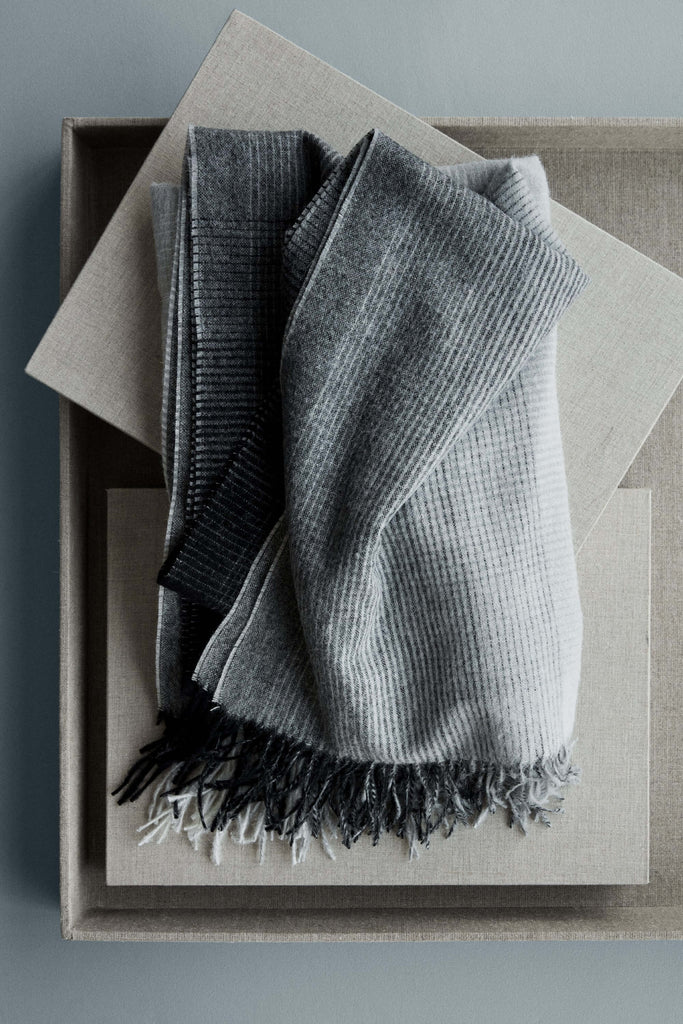 A gray ombre throw blanket is folded and sits on a natural linen box.