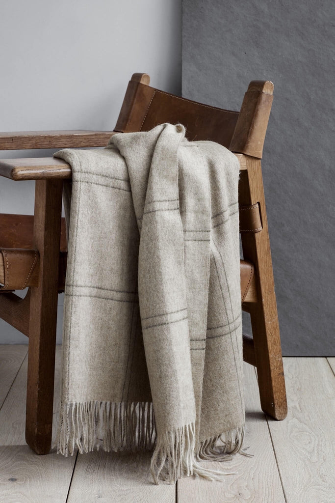 A beige alpaca throw with a large check pattern drapes over the side of a wood and leather chair.