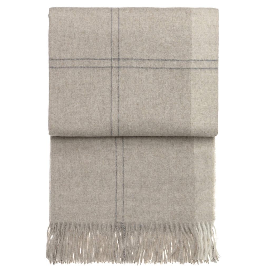 Folded beige alpaca throw blanket on a white background. The blanket has a subtle darker check pattern.