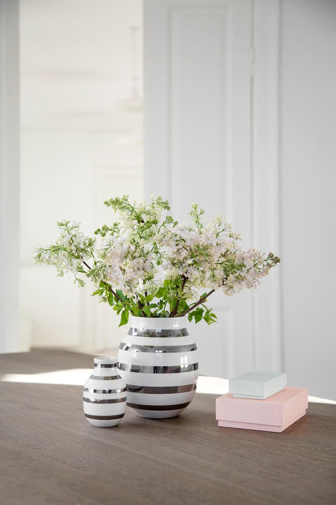 Two metallic silver and white stripped vases of different sizes sitting on a wood table. The larger vase holds white flowers.