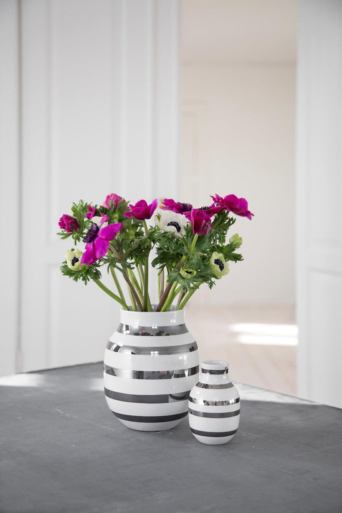 Two metallic silver and white stripped vases of different sizes sitting on a table. The larger vase holds magenta and white flowers.