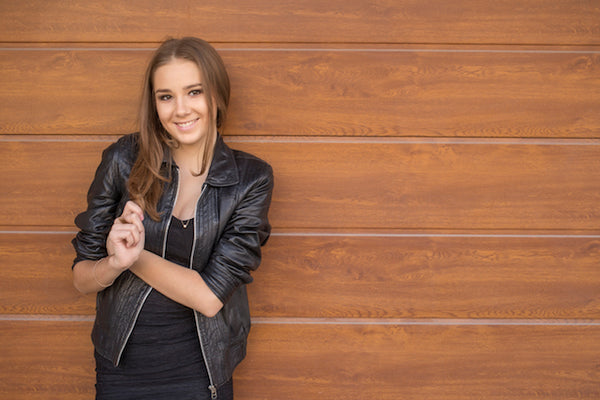 girl in black leather jacket against wood wall