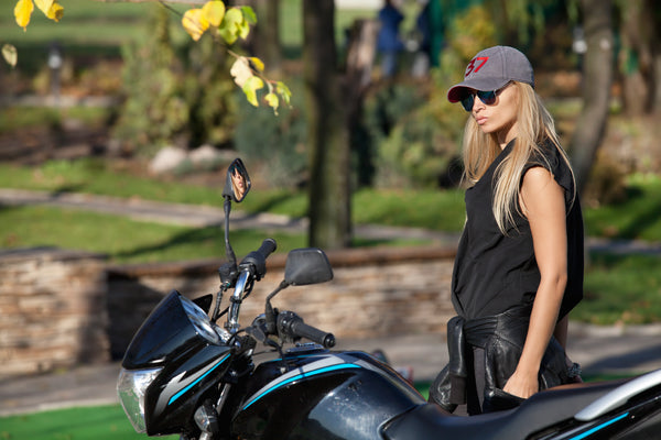 woman in baseball cap with motorcycle