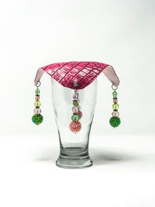 pink crocodile skin textured drink cover with green and pink beads on glass