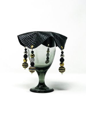 black crocodile skin textured drink cover with white and crimson beads on glass,