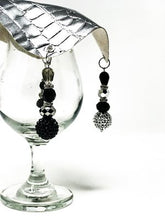 Matte black beads with silver beads dangle off each corner of the drink cover