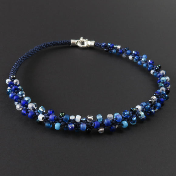 Braided necklace - Blue and white beads on dark blue (spiral)