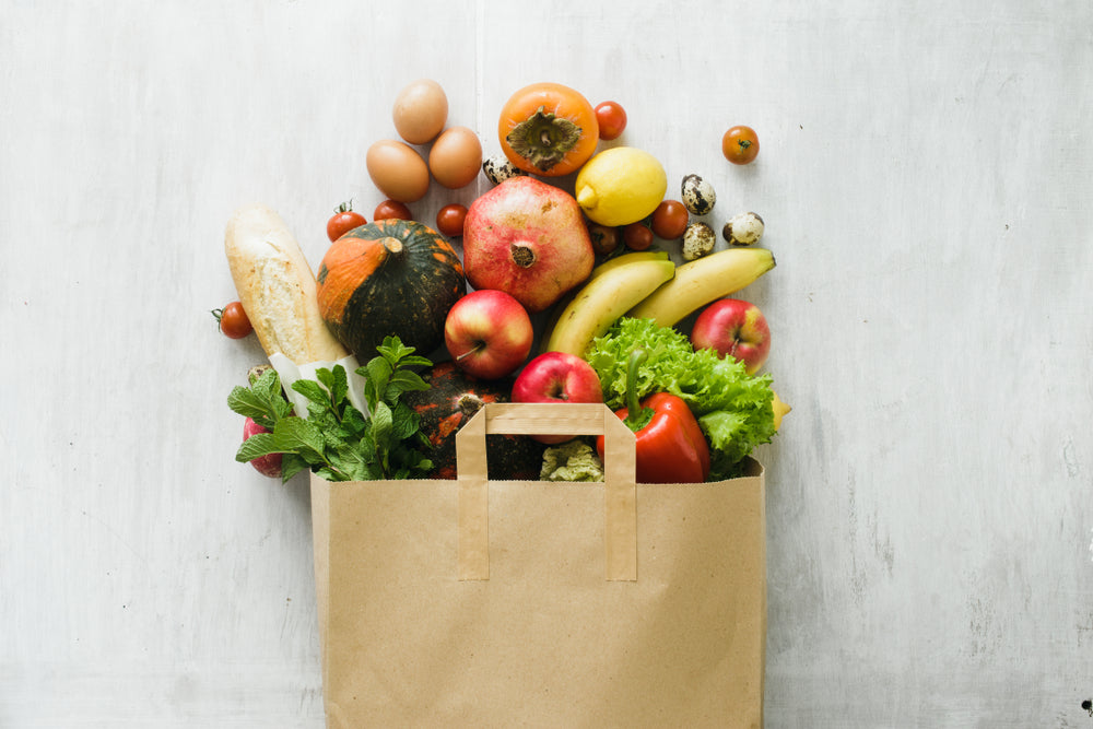 Paper bag full of healthy groceries including fruits and vegetables