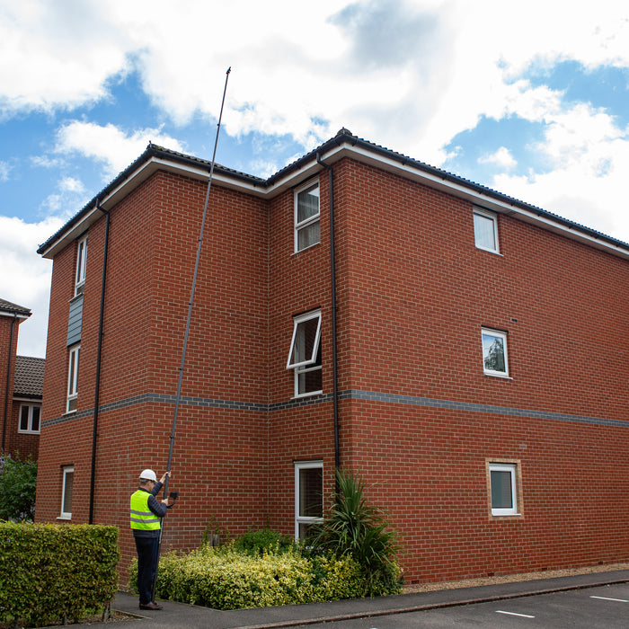 Single operator using a 35ft 10m five storey camera pole system for roof inspection, made by Vantage Point Products