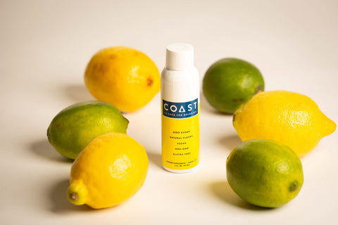 Coast Drink (Coast Health) natural ingredients. Coast drink bottle surrounded by natural lemons and limes. Coast's ingredients are natural and scientifically engineered to make drinking healthier.