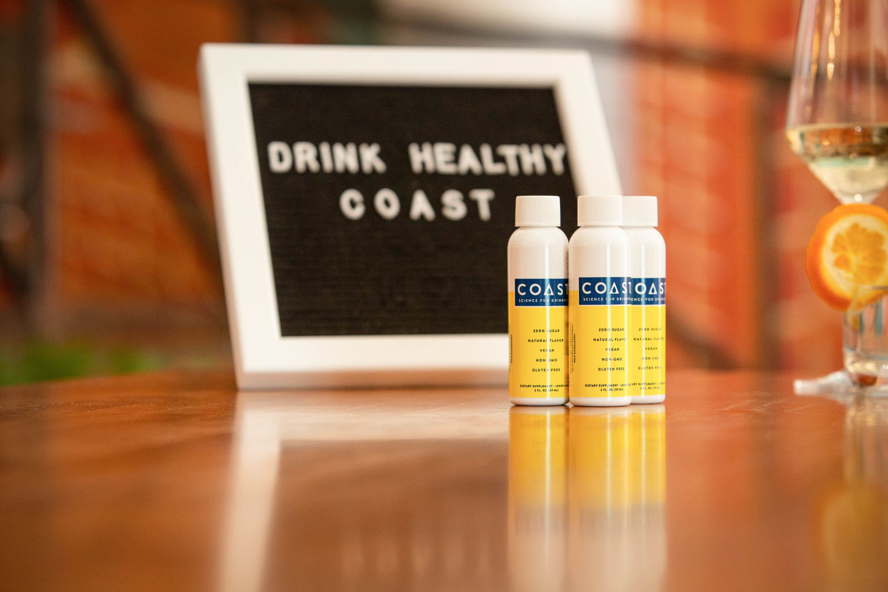 Bottles of Coast Drink (Coast Health) in front of sign saying