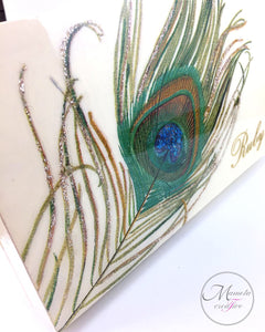 Close up look at the decoupage peacock feather with personalization on top of box - Mamota Creative