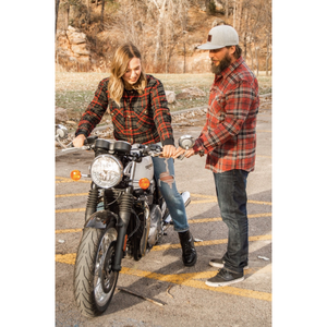 Two people riding a motorcycle while one of them is wearing the Bowery flannel.