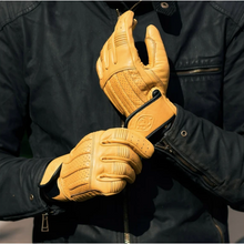 "Load image into Gallery viewer, Close up photo of person wearing the ""Sprint"" gloves in dune yellow adjusting the large velcro straps at the wrist."