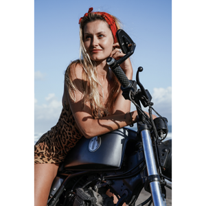 "Close up photo of a person sitting on a motorcycle wearing the red ""Summer Butts"" bandana in their hair as a headband."