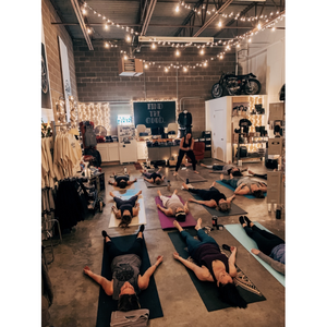 Photo of people doing yoga in a motorcycle shop.
