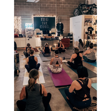 Load image into Gallery viewer, Photo of people doing yoga in a motorcycle shop.
