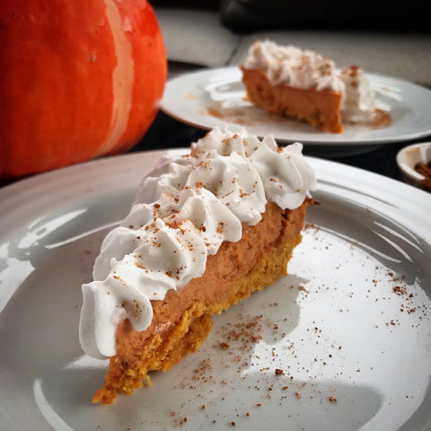 Two pieces of Shanti Chai Pumpkin Pie topped with coconut cream, in front of a winter squash.