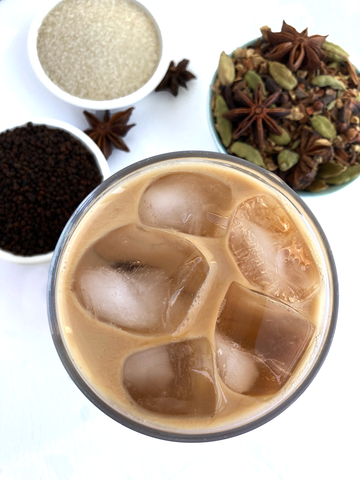 Iced Original Chai Blend, from Shanti Chai & Co. Chai poured over ice, with chai spices, Assam tea and a few star anise pods below.