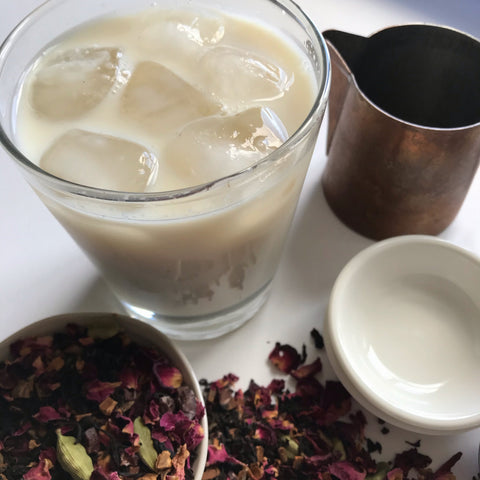 A cup of Iced Chai, made with simple steep method. Shanti Chai & Co's Rose Petal Chai was used for this iced chai. A copper carafe for milk, a glass of iced chai, a white bowl of rose petal chai.