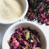 Raw sugar and Shanti Chai & Co's Rose Petal Chai sit in white bowls against a backdrop of rose petals and Assam tea.