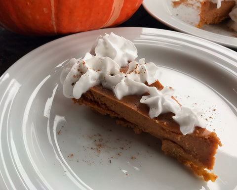 A freshly made piece of Shanti Chai Pumpkin Pie, topped with whipped coconut cream.