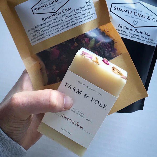 "A hand holds Shanti Chai & Co's ""All Rose"" Gift Set of Rose Petal Chai, Nettle & Rose Tea and Coconut Rose soap from Farm & Folk."
