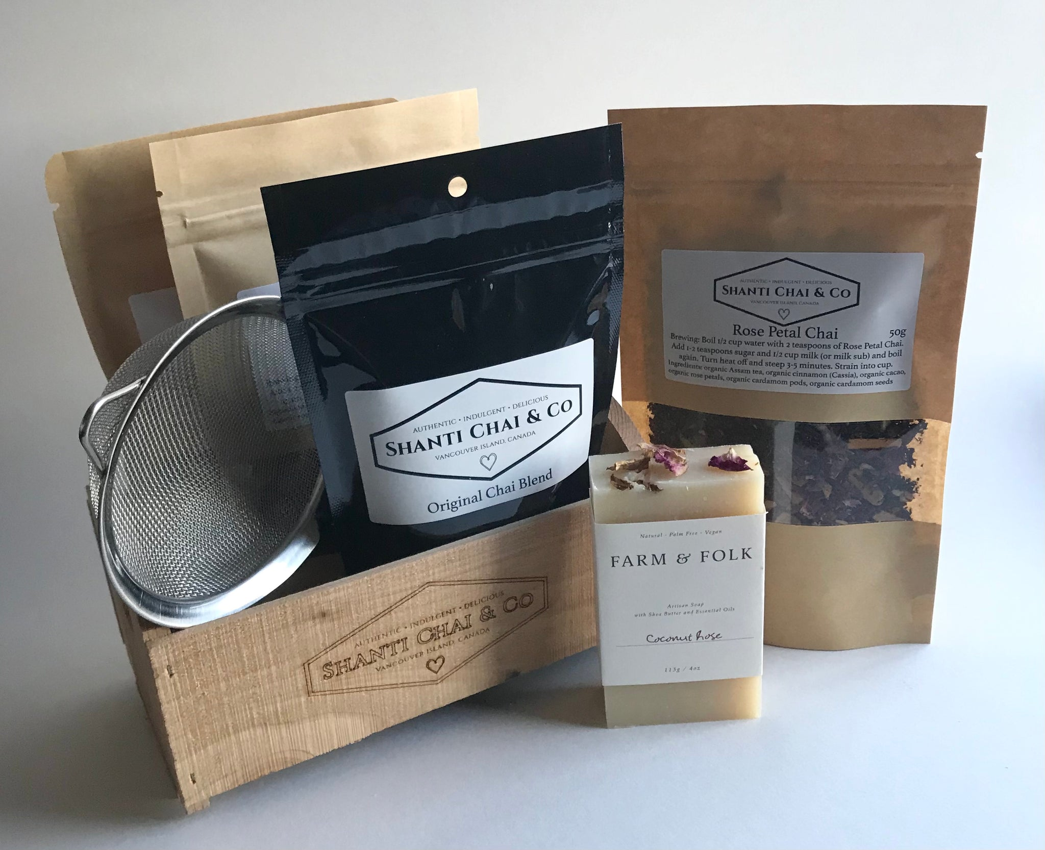 The Chai Lover's Gift Set, from Shanti Chai & Co. Includes: Original Chai Blend (50g), Rose Petal Chai (50g), Candied Ginger Chai (50g), Golden Turmeric Chai (50g), a stainless steel tea strainer, a bar of Coconut Rose soap from Farm & Folk and a mini handmade crate from local company Yonderwood.