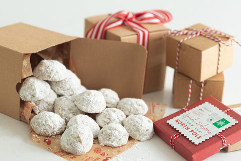 keto snowball cookies spilling out of kraft paper box tied with red and white ribbon