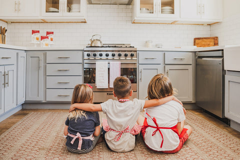 three kids sitting in front of oven waiting for homemade chocolate chip cookies