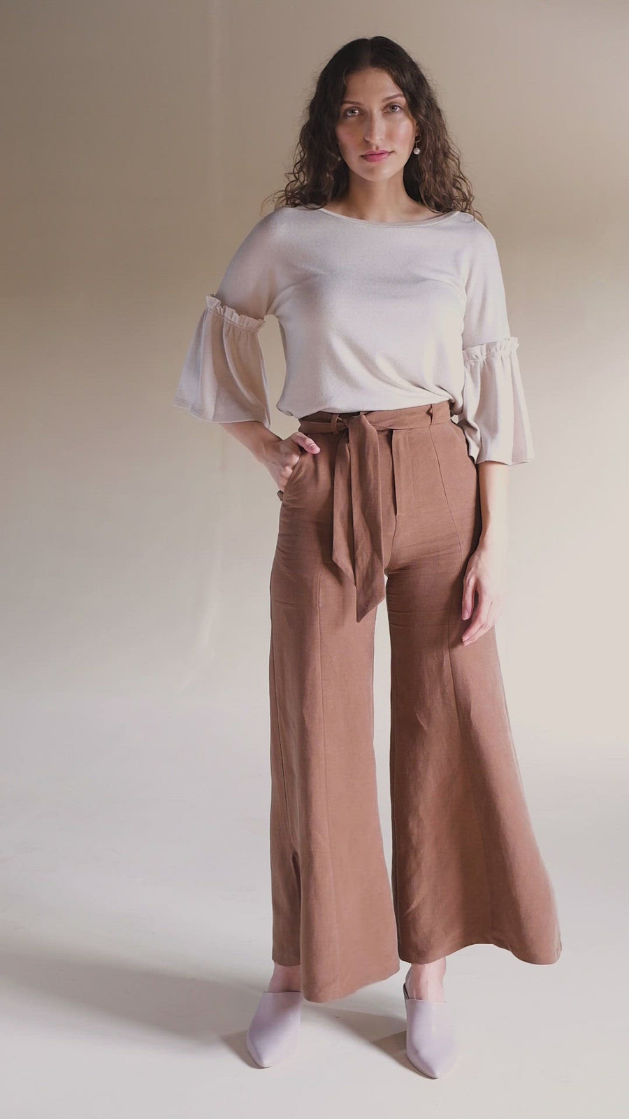 Model wearing Akala Clothing's sustainable wide leg pant in Rust Brown color, size Extra Small