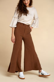 Front view of model wearing Akala Clothing's sustainable wide leg pant in Rust Brown color, size Extra Small